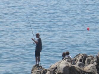 MAN FISHING ON ROCKS